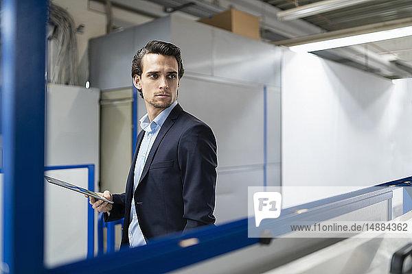 Geschäftsmann mit Tablette in einer Fabrik  der sich umsieht