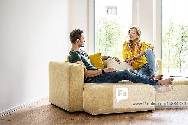 Paar sitzt in seinem neuen Zuhause auf der Couch und diskutiert