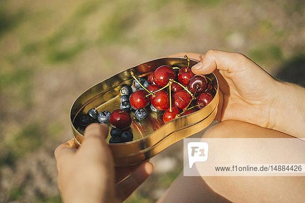 Frau hält Dose Kirschen und Blaubeeren in der Hand  Nahaufnahme