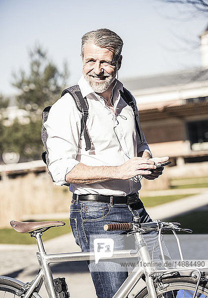 Portrait of smiling mature businessman with bicycle  cell phone and earphones