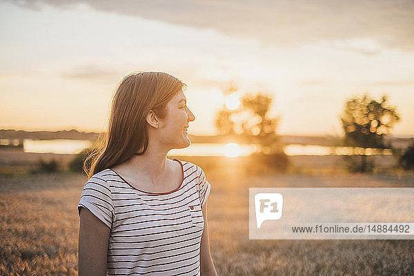 Lächelnde junge Frau genießt Sonnenuntergang in der Natur