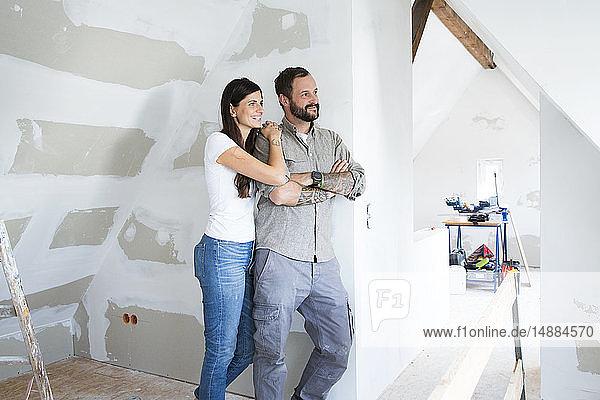 Lächelndes Paar auf dem Dachboden  das renoviert wird und aus dem Fenster schaut