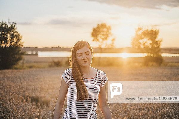 Porträt einer jungen Frau  die sich bei Sonnenuntergang in der Natur entspannt