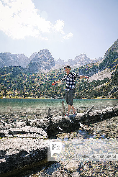 Austria  Tyrol  man balancing on tree trunk at lake Seebensee
