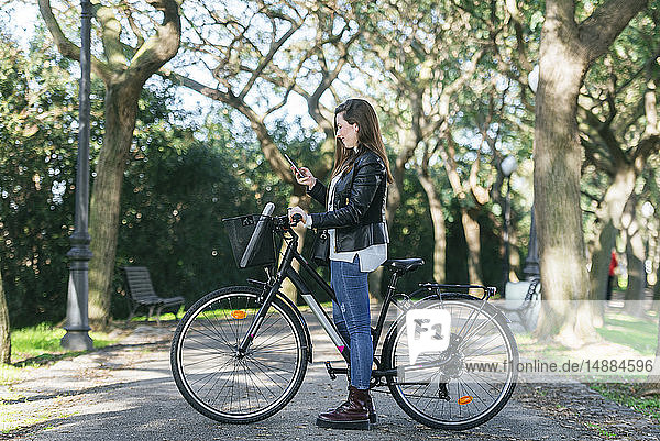 Young woman with bicycle in park using cell phone