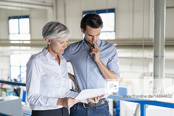 Businessman and senior businesswoman looking at plan in a factory