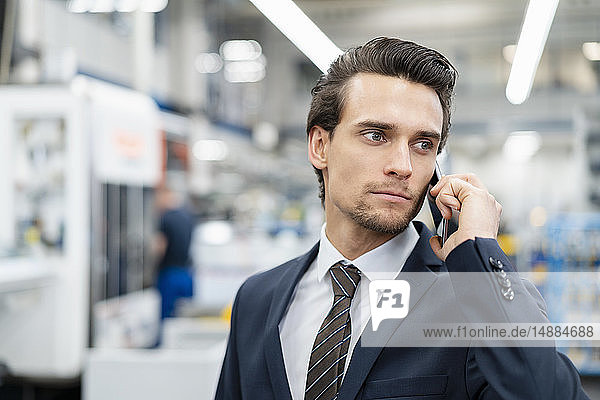 Portrait of businessman on cell phone in a factory
