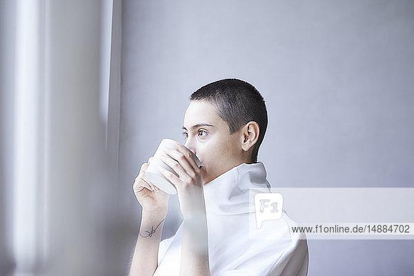 Porträt einer kurzhaarigen jungen Frau  die aus einem Becher trinkt