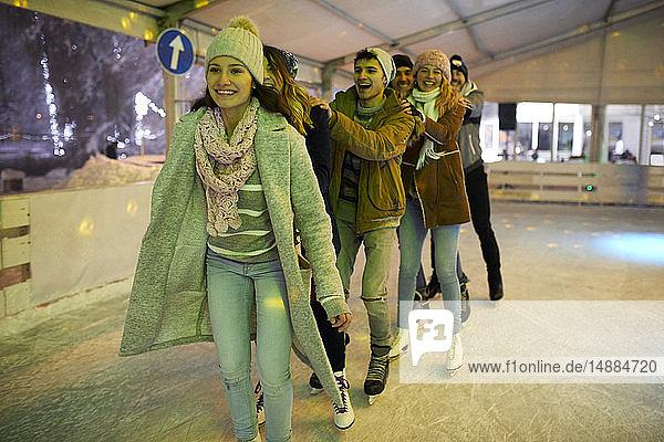 Glückliche Freunde beim nächtlichen Schlittschuhlaufen auf einer Eisbahn