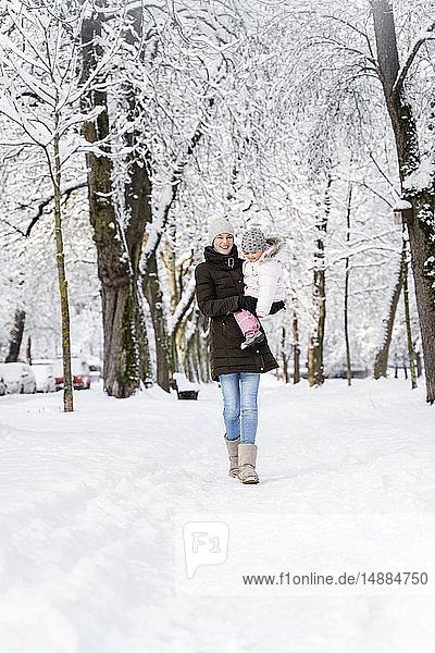 Glückliche Mutter geht mit Tochter in Winterlandschaft spazieren