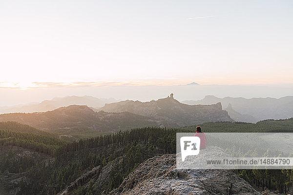 Spanien  Gran Canaria  Pico de las Nieves  Rückenansicht einer Frau  die auf einem Felsen sitzt und die Aussicht betrachtet