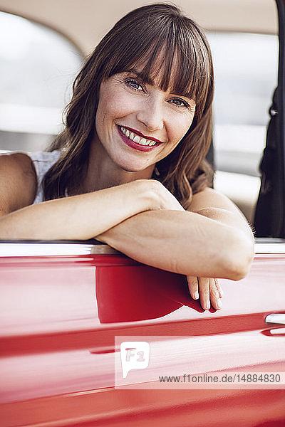 Carefree woman sitting in vintage car  smiling