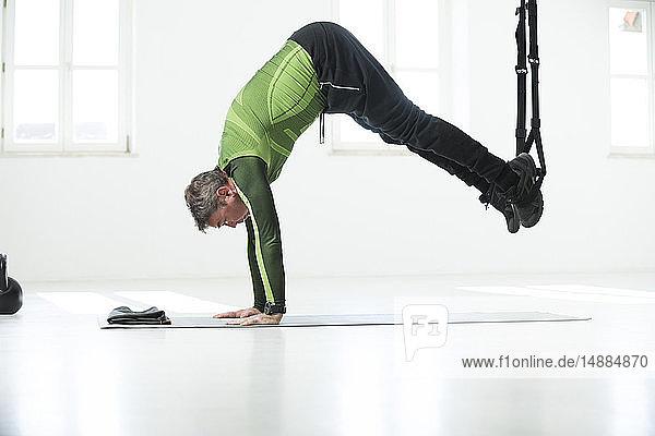 Mann macht sein Fitness-Regime  macht Suspensionstraining