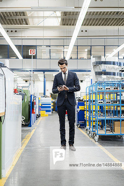 Businessman using cell phone in a factory