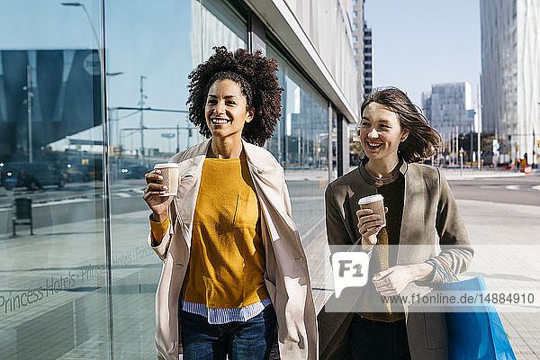 Two happy women with shopping bags and takeaway coffee walking in the city