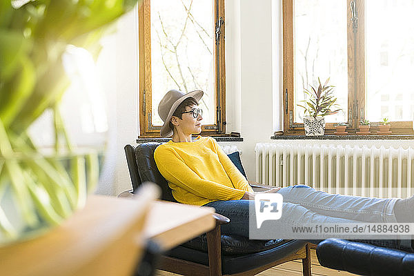 Pensive woman relaxing in lounge chair in stylish apartment looking out of window