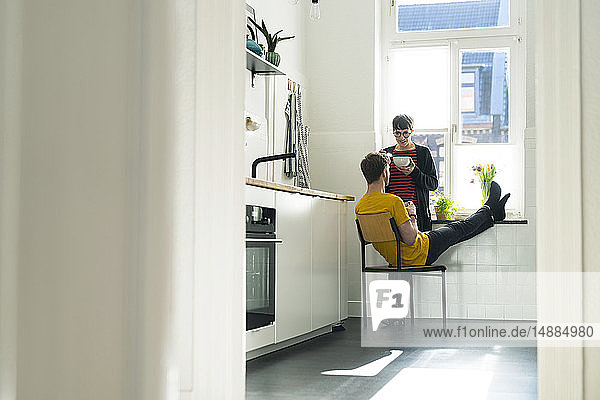 Couple at the window in kitchen at home