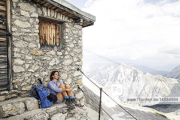 Österreich  Tirol  Frau auf Wanderung mit Rast auf Berghütte