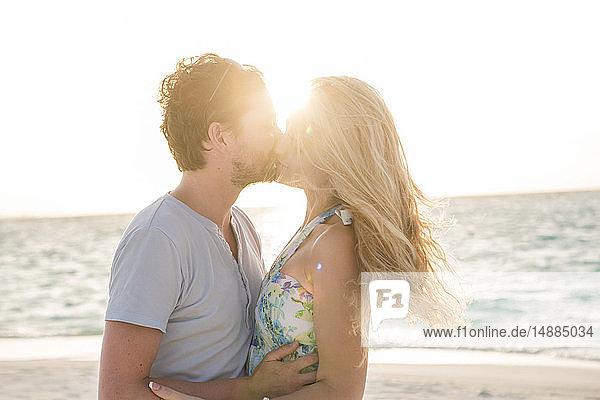 Glückliches Paar küsst sich am Strand