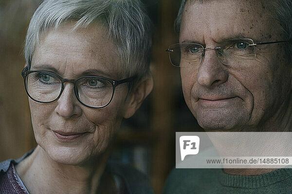 Zuversichtliches älteres Ehepaar schaut aus dem Fenster