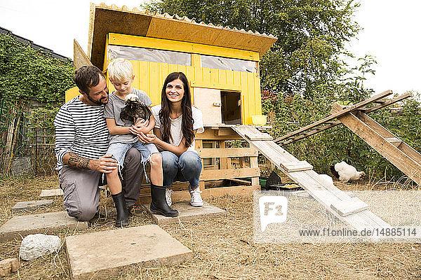 Porträt einer glücklichen Familie mit polnischem Huhn im Hühnerstall im Garten