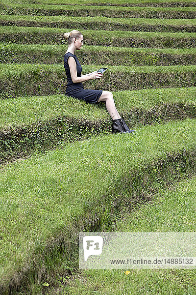 Italy  Alto Adige  Lana  woman sitting on grass-covered steps of natural open air theater using tablet