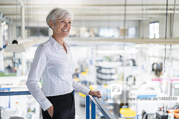 Smiling senior businesswoman on upper floor in factory overlooking shop floor