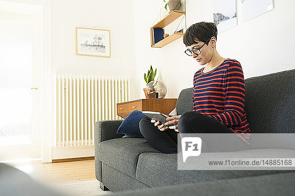 Casual short-haired woman relaxing on lounge couch in modern living room using a tablet