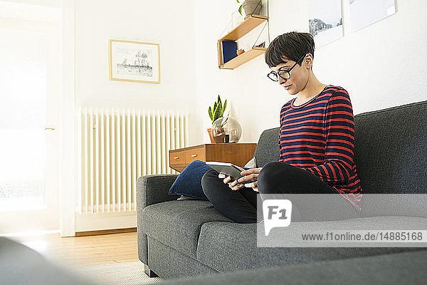 Lässige kurzhaarige Frau  die sich auf einer Lounge-Couch im modernen Wohnzimmer mit Hilfe eines Tablets entspannt
