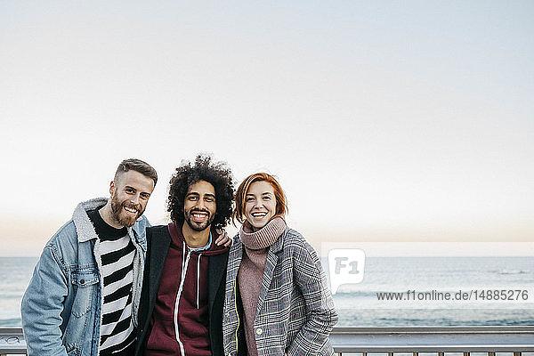 Porträt von drei glücklichen Freunden am Meer