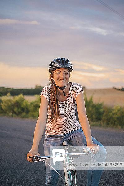 Porträt einer lächelnden jungen Frau mit Fahrrad auf einer Landstraße in der Abenddämmerung