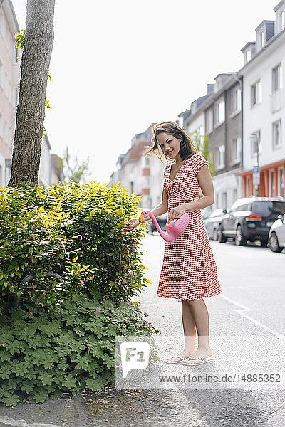 Frau gießt Pflanzen mit einer Flamingokanne in einer städtischen Straße