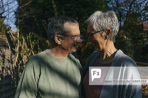 Zärtliches älteres Ehepaar steht sich im Garten gegenüber