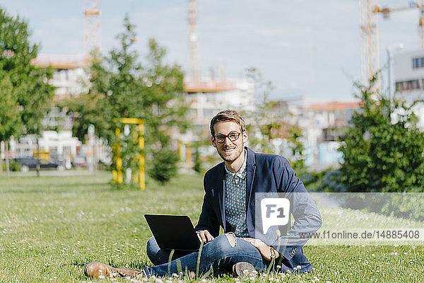 Junger Geschäftsmann sitzt im Park und benutzt einen Laptop