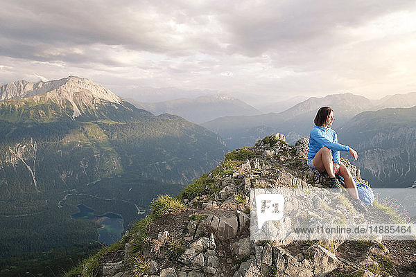 Austria  Tyrol  woman on a hiking trip in the mountains sitting on peak
