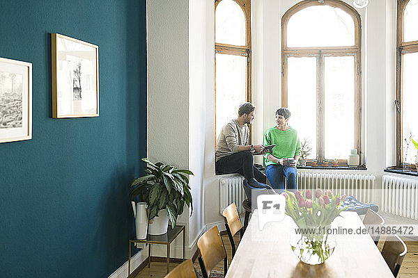 Casual couple having a conversation and sitting at window in stylish apartment