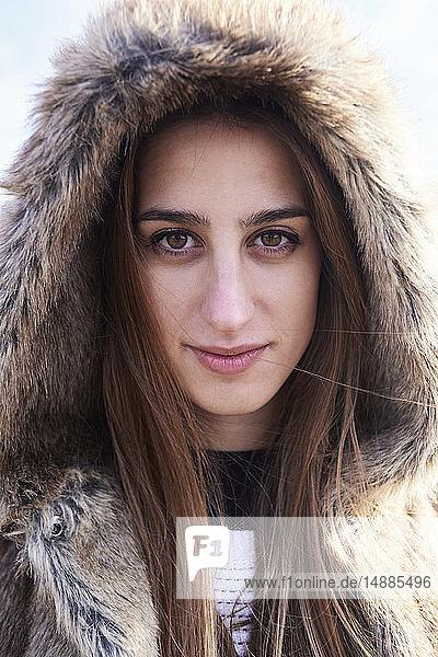 Portrait of beautiful young woman wearing fur hood