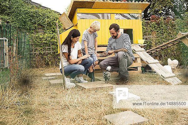 Glückliche Familie mit polnischem Huhn im Hühnerstall im Garten