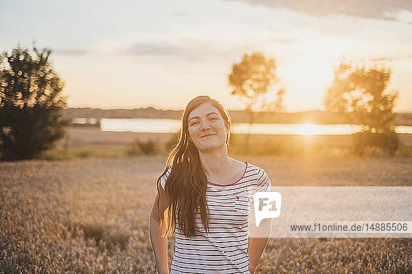 Porträt einer lächelnden jungen Frau in der Natur bei Sonnenuntergang