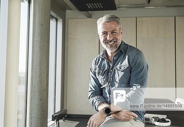 Porträt eines lächelnden lässigen reifen Geschäftsmannes im Amt