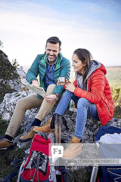 Glückliches Paar auf einer Wanderung in den Bergen macht eine Pause und schaut auf die Karte