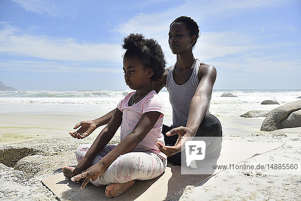 Mother with daughter doing a yoga exercise on the beach