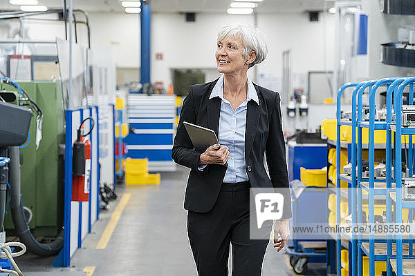 Senior businesswoman with tablet walking in a factory