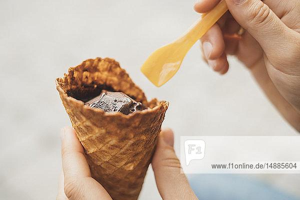 Frauenhand hält Eistütchen mit Schokoladeneis  Nahaufnahme