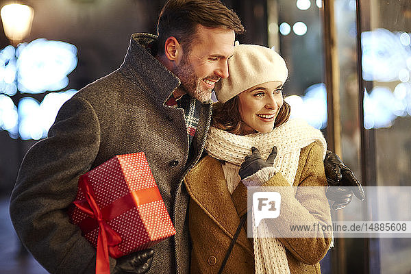 Happy couple looking in shop window at Christmas time