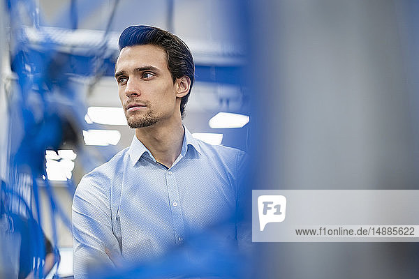 Portrait of businessman in a factory looking around