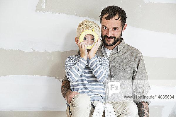 Porträt von Vater und Sohn mit Klebeband beim Dachbodenausbau