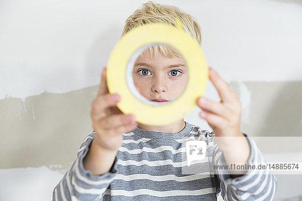 Porträt eines Jungen  der durch Klebebandmaut schaut