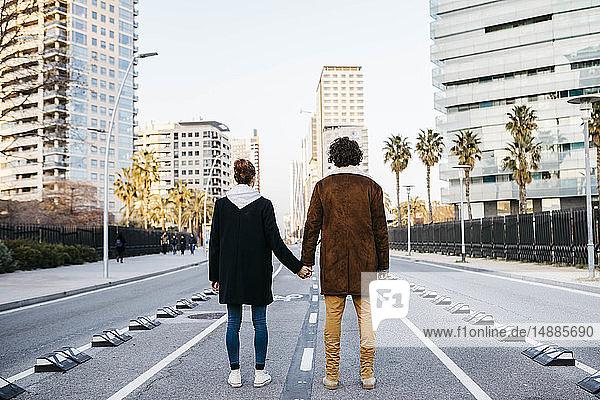 Rückansicht eines Paares  das sich in der Mitte der Straße an den Händen hält und die Gebäude im Hintergrund betrachtet