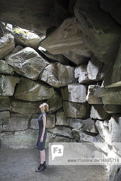 Italy  Alto Adige  Lana  woman standing in stone cave looking up